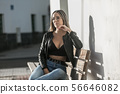 Woman sitting with hand on chin 56646082