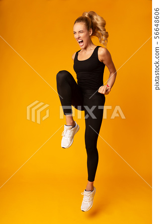 Skinny Girl Jumping Expressing Aggression Over Yellow Studio Background 56648606