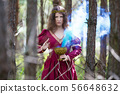 Woman in a red dress casting a spell with smoke 56648632