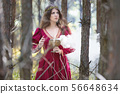 Woman in a red dress casting a spell with smoke 56648634