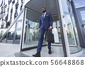 Confident Afro Businessman With Briefcase Leaving Modern Office Building 56648868