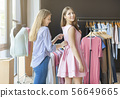 Shop assistant helping female customer with zipper at clothing store 56649665