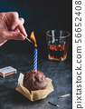 Hand lighting candle on birthday muffin 56652408