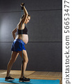 Pregnant woman exercising with resistance band 56653477