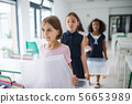 Group of cheerful small school kids with plastic trays in canteen, walking. 56653989