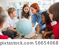 A group of small school kids with teacher sitting on the floor in class, learning. 56654068