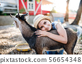 A portrait of small girl outdoors on family animal farm, hugging goat. 56654348