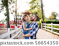 A father with small daughter standing outdoors on family farm, playing with hat. 56654350