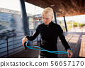 A young sportswoman doing exercise outdoors, skipping. 56657170