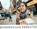 asian woman eat takoyaki with lovely smile 56663730