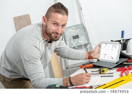 smiling young handyman using computer tablet, DIY 56674958