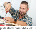 smiling young man using screwdriver at home 56675013