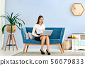 Young woman using laptop while sitting on sofa 56679833