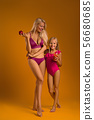 blonde mom holds an apple and her daughter in swimsuit drinks fresh juice. 56680685