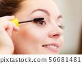 Woman applying black eye mascara to her eyelashes 56681481