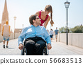 Woman and disabled man having a walk 56683513
