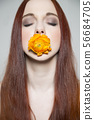 Beautiful young girl with yellow rose in her mouth 56684705