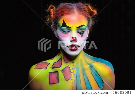 Beautiful lady with a face painting clown posing 56688091