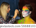 The artist puts a face painting on a lovely young 56688103