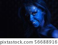 Young cute girl with blue face painting. 56688916