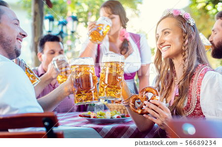 Couple clinking glasses with huge amounts of beer in Bavarian pub 56689234