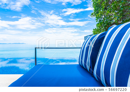 Beautiful luxury outdoor swimming pool with sea ocean view on blue sky white cloud around pillow on sofa decoration