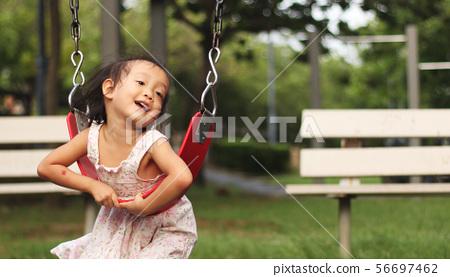 一位開心的亞洲女孩在公園盪秋千 56697462