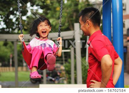 一位開心的亞洲女孩在公園盪秋千,爸爸幫她推秋千,父親節和兒童節背景圖 56702584