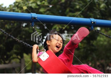 一位開心的亞洲女孩在公園盪秋千,爸爸幫她推秋千,父親節和兒童節背景圖 56702593