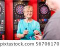 Mature woman holding dartboard arrows 56706170