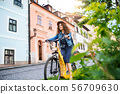 Beautiful young woman tourist traveller with electric scooter in small town. 56709630