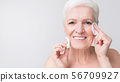 Charming senior woman cleansing her face with cotton pads 56709927