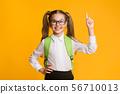 Smiling nerdy schoolgirl pointing finger up having idea, yellow background 56710013