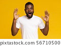Surprised and shocked african american guy standing with opened mouth 56710500