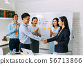 Young business people shaking hands and cheering crowd clapping background 56713866
