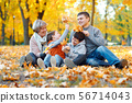 Happy family sitting on fallen leaves, playing and 56714043