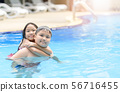 Brother and sister play water in swimming pool 56716455