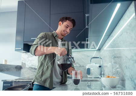 Handsome man pouring coffee into cup in the morning 56731880