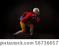 Side view of running girl in white helmet with rugby ball in her hand in studio 56736657