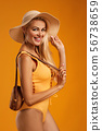 cute blonde girl in orange swimsuit posing 56738659