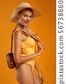 cute blonde girl in orange swimsuit posing 56738660
