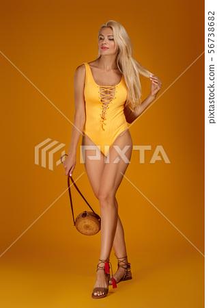 cute blonde girl in orange swimsuit posing 56738682