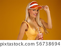 blonde girl in a bathing suit and hat holding a cocktail 56738694