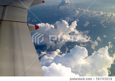 Blue skies and sun, as seen through an aircraft window in flight 56743019