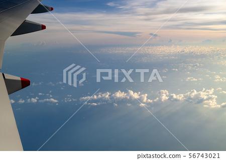 Blue skies and sun, as seen through an aircraft window in flight 56743021