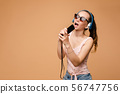 Girl in headphones listening music and singing 56747756