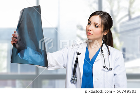 Female doctor examining a lung radiography 56749583
