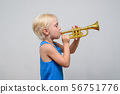 Little cute blond boy playing toy trumpet on light 56751776