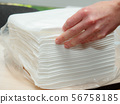 Opened pack of white paper napkins and females 56758185
