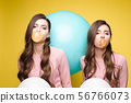 Young twins holding pink and white balloons in 56766073